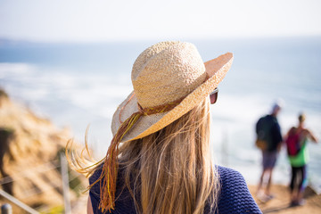 Young, blonde female, girl in a straw hat on the sun. California. Spring. Pacific ocean. California