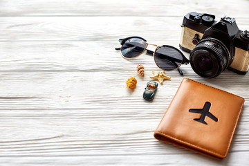 travel and wanderlust concept, summer vacation background, space for text. photo camera sunglasses passport  car shells on white wooden table. planning summer holiday