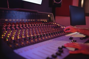 Hands of male audio engineer using sound mixer