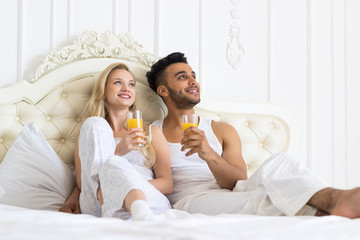 Young Couple Drink Orange Juice Sitting Bed, Happy Smile Young Hispanic Man And Woman dream Look Up Copy Space Lovers Hold Glasses Bedroom
