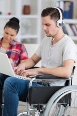 man with laptop on wheelchair with woman aside