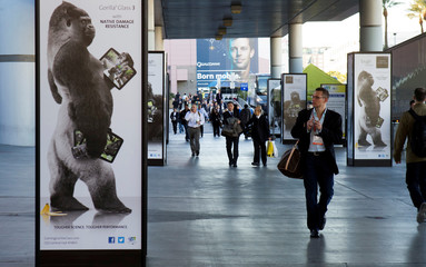 FILE PHOTO: Man walks by advertisement for Corning Gorilla Glass 3 outside Las Vegas Convention Center on first day of Consumer Electronics Show in Las Vegas