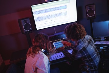 Rear view of audio engineers using digital tablet in studio