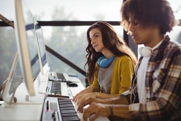 Audio engineer playing electric keyboard