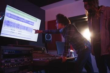 Male audio engineers using sound mixer