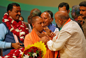 India's ruling Bharatiya Janata Party leader Yogi Adityanath is offered sweets after he was elected as Chief Minister of India's most populous state of Uttar Pradesh, during the party lawmakers' meeting in Lucknow