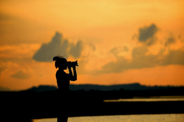 silhouette photo , woman photographer shooting a sunset