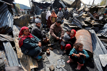 People sit through the remains of their houses gutted in a fire which broke out in a residential area on Tuesday, in Srinagar