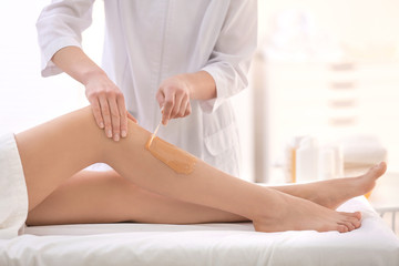 Beautician waxing female legs in spa center