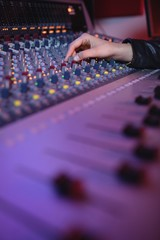 Hands of female audio engineer using sound mixer