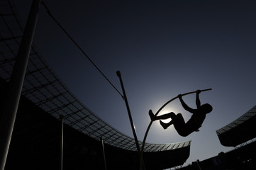 A pole vaulter makes a jump while silhouetted against the sun during an athletics competition
