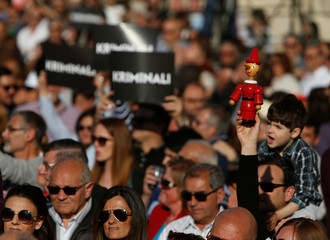 """A protestor holds up a toy Pinocchio as others hold signs reading """"Criminals"""" during a national protest against the government of Prime Minister Muscat, in Valletta"""
