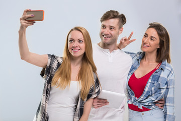 Casual People Group, Young Man Two Woman Happy Smile Taking Selfie Photo Cell Smart Phone Network Communication Over Grey Background