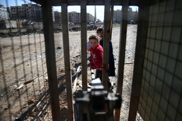 Children press a lever to fill water containers in the rebel-held besieged Douma neighbourhood of Damascus