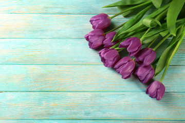 Beautiful bouquet of lilac tulips on color wooden background