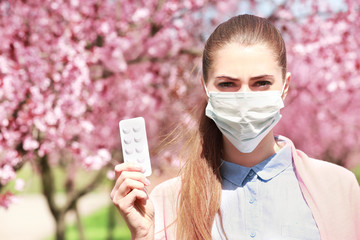 Young girl wearing face mask and holding pills among blooming trees in park
