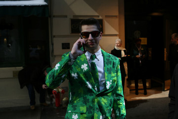 A paradegoer wearing a green clover suit poses for a picture during the St. Patrick's Day Parade in New York City