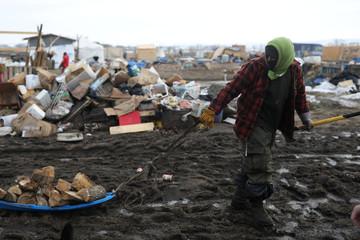 A man uses a sled to transport firewood in the recently closed Oceti Sakowin camp before the police raid in Cannon Ball