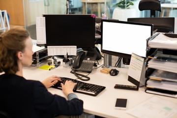 Businesswoman working on desktop pc at office