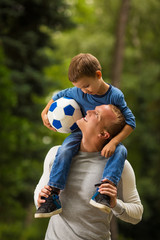 Dad and a little son with a soccer ball walking in park and smiling