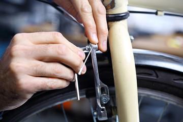 Mężczyzna  wymienia klocki hamulcowe w rowerze