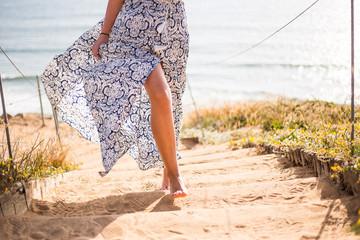 Female, woman leg, legs, feet, feets in the blue dress running near sand, grass. Summer wibes. Sun
