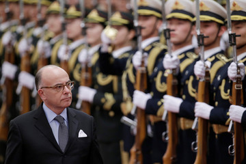 French Prime Minister Bernard Cazeneuve inspects honour guards during a welcoming ceremony in Beijing