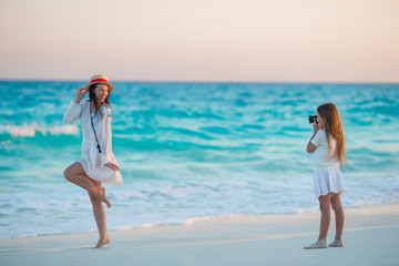 Little cute girl taking photo of her mom at tropical beach