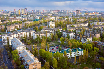 The aerial View of urban residential district in Kyiv,Ukraine in spring.View over the city rooftops with sunlight at Darnitsa suburb.Moderns buildings at Industrial uptown;residential neighbourhood.
