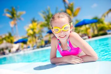 Portrait little girl having fun in outdoor swimming pool