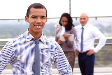 Holding a tablet, a young handsome black businessman is standing outside of a business building, confidently looking forward.