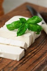 sliced feta cheese decorated with fresh basil leaf on a wooden board. close up and selective focus
