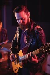 Musician playing electronic guitar in studio