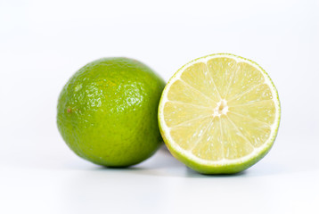 half lime and whole lime over white background with copy space