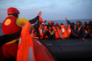 A rescuer hands out life jackets to migrants crowding a plastic raft while drifting, during a search and rescue operation by Spanish NGO Proactiva Open Armsin in central Mediterranean Sea