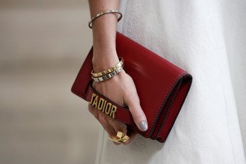 A guest holds a handbag as she arrives to attend the French fashion house Christian Dior Fall/Winter 2017-2018 women's ready-to-wear collection during Fashion Week in Paris