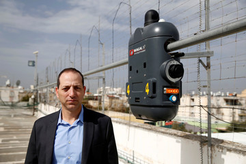 Saar Koursh, Chief Executive Officer at Magal Security Systems, poses for a picture near one of their products, RoboGuard, which is a surveillance robot, seen on exhibit atop the roof of their offices in Yahud, Israel