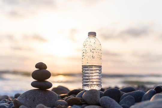 Plastic bottle of water on the beach at sunset , sunrise time