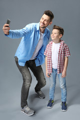 Father and son having fun on color background