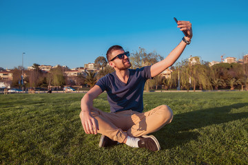 Handsome man in sunglasses doing selfie in the park.Bearded man sitting on a green grass,black sneakers,man dressed in casual wear,man relaxing,outdoor portrait of happy man,sunny portrait,attractive