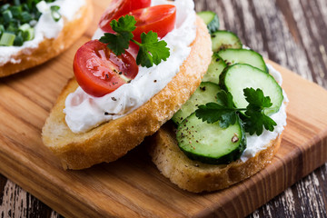 Sandwiches with cream cheese, cucumbers and tomatoes