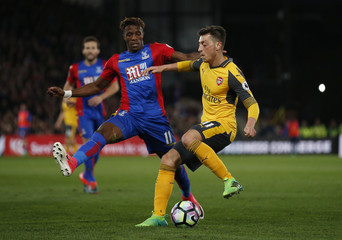 Crystal Palace's Wilfried Zaha in action with Arsenal's Mesut Ozil
