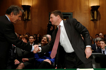 Brown greets Clayton as he takes his seat to testify at a Senate Banking, Housing and Urban Affairs Committee hearing on his nomination of to be chairman of the Securities and Exchange Commission (SEC) on Capitol Hill in Washington
