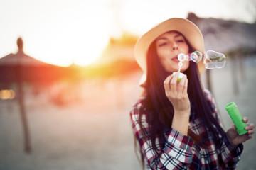 Beautiful brunette wearing hat blowing dreamy bubbles