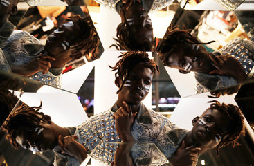 A visitor poses for a picture next to mirrors during Sao Paulo Fashion Week in Sao Paulo