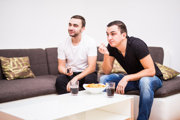 Friends enjoying soccer in TV with drinks and snacks on sofa