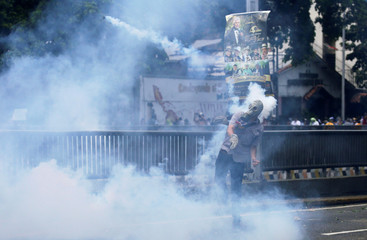 Demonstrator throws back a tear gas canister while clashing with the riot police during a rally in Caracas, Venezuela