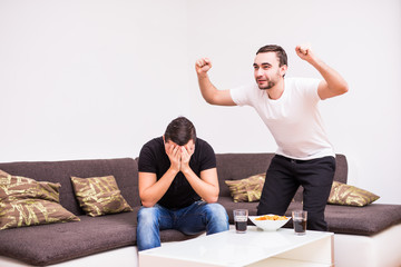 happy male friends supporting football team at home. One man happy, another sad.