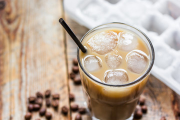 Ice coffee with milk and beans for lunch on wooden background