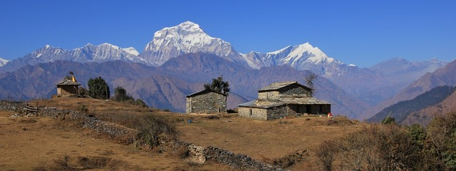 Fotorollo Nepal Autumn day in the Himalayas. Seventh highest mountain of the world, Dhaulagiri. Old stone house and shed.